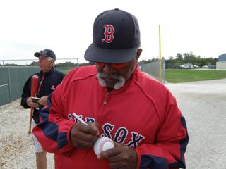 Luis Tiant autographs a baseball.