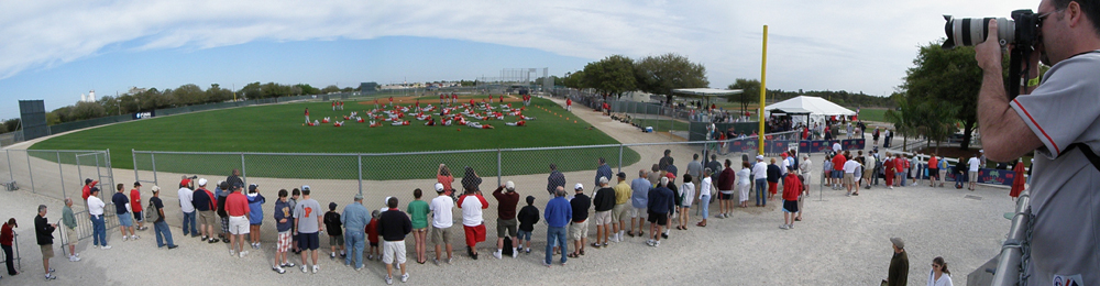 Panoramic view of the players hard at work stretching, and the fans hard at work watching them.