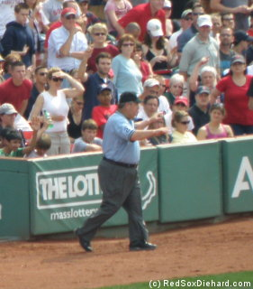 After reviewing the play, crew chief Joe West signals that the ball was foul.