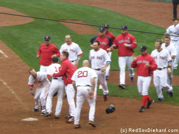 Nick Green's teammates prepare to meet him at home plate. Jonathan Papelbon is attacking George Kottaras, and Dustin Pedroia has just throw his helmet at Kevin Youkilis.