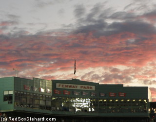 The sun sets over the Fenway facade before the game.