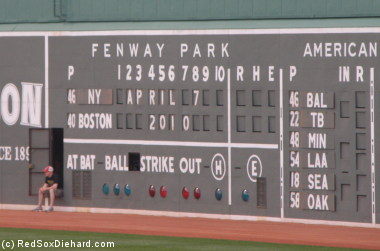 In can get hot insode the Fenway Park scoreboard, so the guy who posts the score takes the chance to get some fresh air before the game starts.