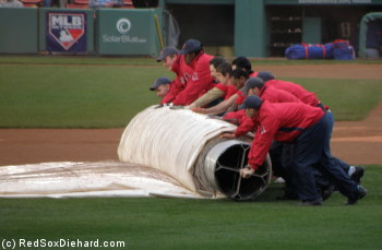 The grounds crew rolls up the tarp.