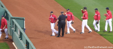 The relievers have fist bumps for bullpen cop Billy Dunn as they make their way in before the game.