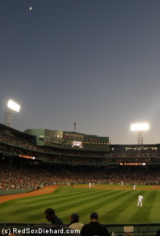 The moon rises over Fenway Park.