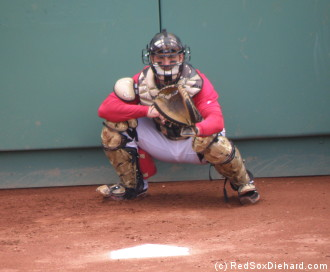 Jason Varitek warms up in the bullpen wearing the camouflage catcher's gear he'll auction off after the game.  He drilled his 7th home run of the year in the 8th inning.
