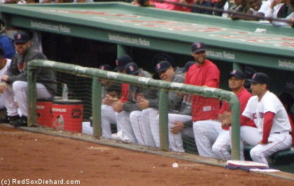 In the Red Sox dugout, Pedroia cracks his teammates up. On the far left is Kevin Youkilis with his injured hand in a bandage.