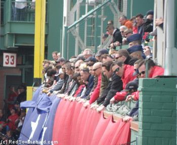 Everyone in the from row of the Green Monster seats gets to help hold the giant American flag.