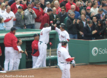 Dustin Pedroia, human laser show, is greeted by David ortiz afte his firs inning home run.