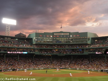 The Royals bat against Andrew Miller as the sun sets over Fenway Park.