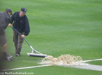 The grounds crew uses rollers to try to push a giant lake out of the outfield.