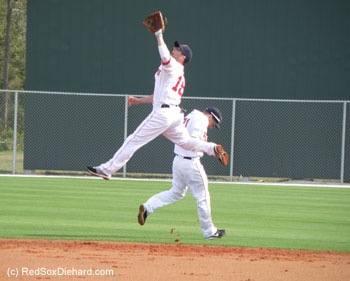 Dustin Pedroia leaps to catch a ball during one of the drills, while his second base counterpart Nate Spears ducks out of the way.