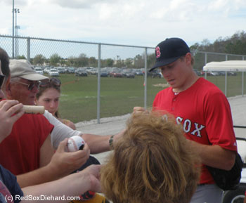 New reliever Mark Melancon signs autographs after practice.