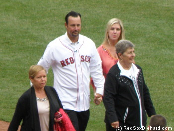 Tim Wakefield walks across the field before the ceremony with his wife, his mother-in-law, and his mother.