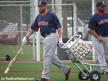 New left fielder Jonny Gomes wheels out a basket of balls for batting practice.