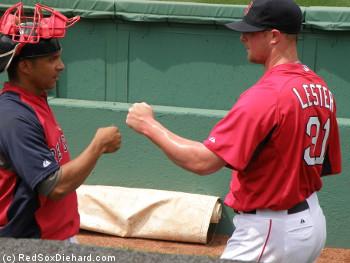 Jon Lester has a fist-bump for bullpen catcher Mani Martinez after finishing his bullpen session.