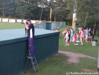 As fans watch from the outfield, the official photographer uses a stepladder to station himself behind the dugout. Then when he took a break for a couple of innings, he let me stand there.
