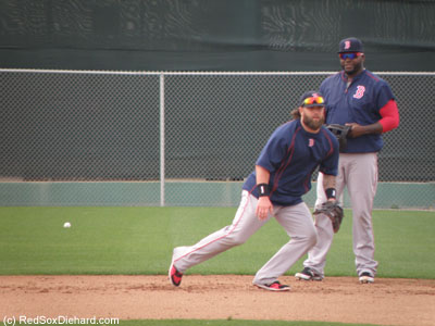 Mike Napoli fields a ball at first base as Big Papi waits his turn.