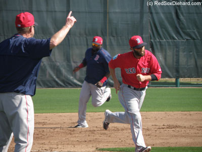 Third base coach Brian Butterfield waves in Dustin Pedroia and David Ortiz in a baserunning drill.  Butterfield would call out the number of outs and players had to practice tagging up and scoring.