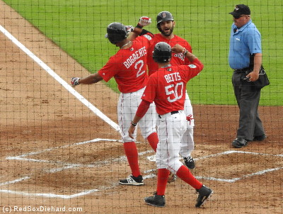 Mookie Betts and Xander Bogaerts greet Mitch Moreland at the plate after his three-run homer.