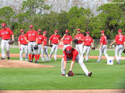 Heath Hembree fields a ball as the other pitchers look on in PFP.