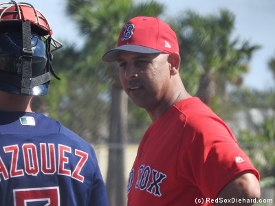 Alex Cora discusses a base-running drill with Christian Vazquez.