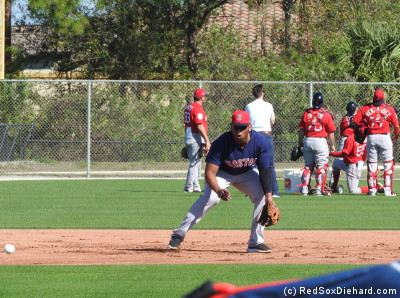 Rafael Devers fields a ball at third. Behind him, in left field, Jason Varitek watches as the catchers participate in a pop-up drill.