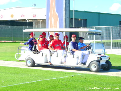 All aboard! The catchers hitch a ride to the far side of the complex for their drills.