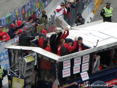 Pedro Martinez, who serves as a special instructor, holds one of the trophies aloft as he rides on a duck boat with Red Sox management.